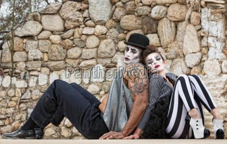 clowns ruecken an ruecken sitzen