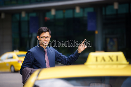 asian businessman calling taxi car leaving