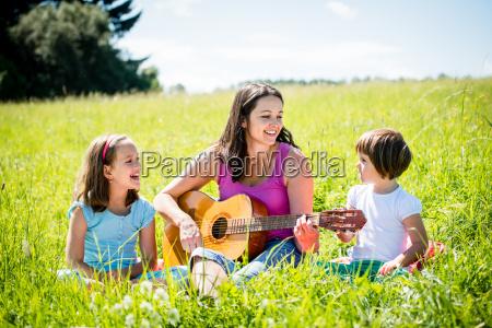 mutter spielt gitarre in der natur