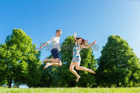 paar springt verliebt auf park wiese