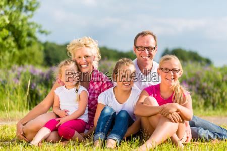familie sitzt im grass auf feld
