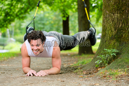 man in city park doing suspension