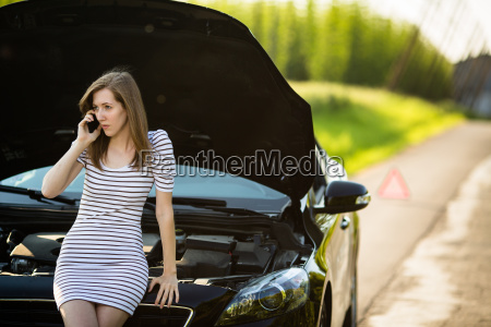 pretty young woman calling the roadside
