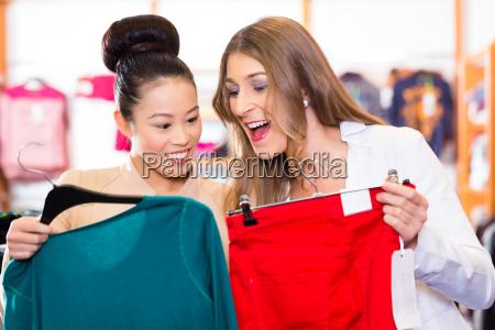 freundinnen shoppen kleidung im laden