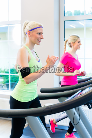 frauen im fitness studio auf laufband
