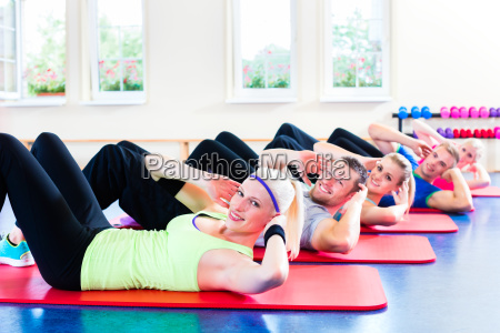 fitness people in gym doing crunches