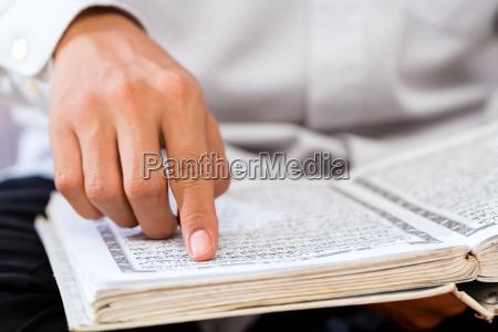 asian muslim mann studiert koran oder