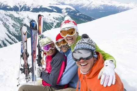 laechelnde freunde sitzen mit skiern im