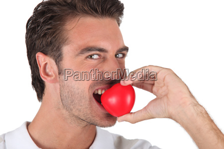 man biting heart shaped object