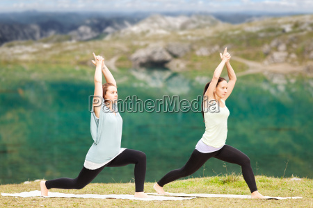 two women doing yoga in front