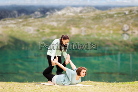 female yoga teacher offers assistance in