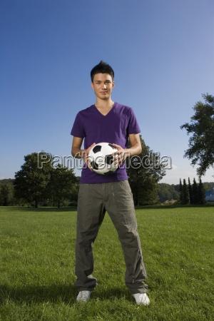 ein teenager mit einem fussball stehen