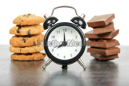 black alarm clock and sweets