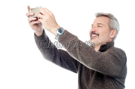 happy aged man taking pictures of