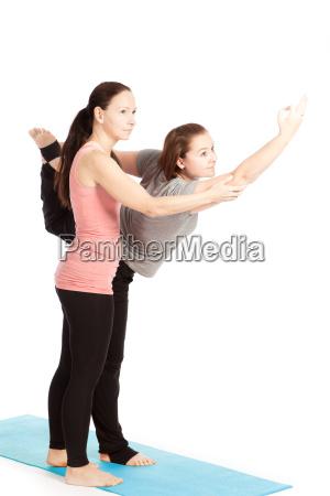 yogalehrerin gibt hilfestellung beim training shiva