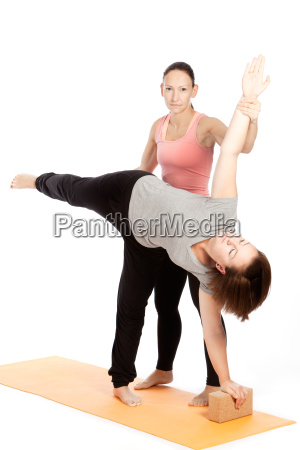 yogalehrerin gibt hilfestellung beim training ardha