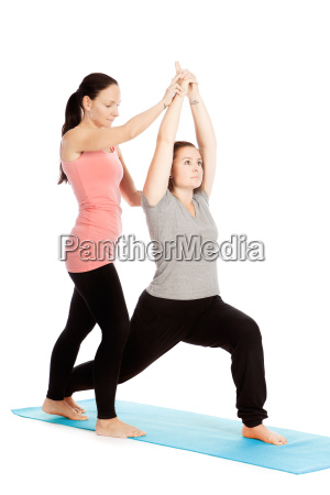 yoga teacher gives assistance during training