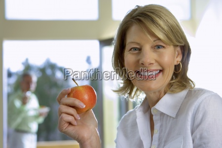 mature woman eating apple at home