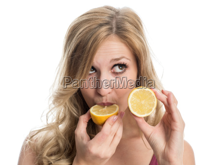 woman biting into lemon