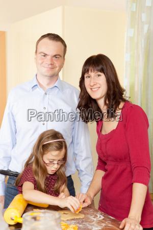 familie backt weihnachtskekse in der kueche