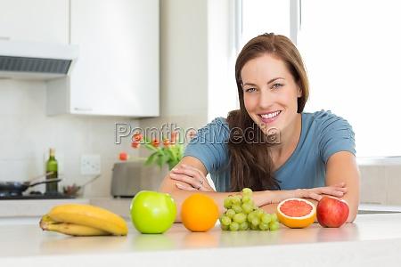 laechelnde frau mit fruechten auf kuechentheke