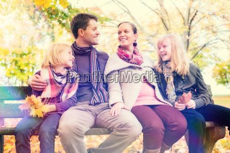 glueckliche familie sitzt auf parkbank im