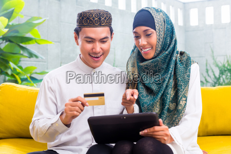 asian muslim couple shopping online on