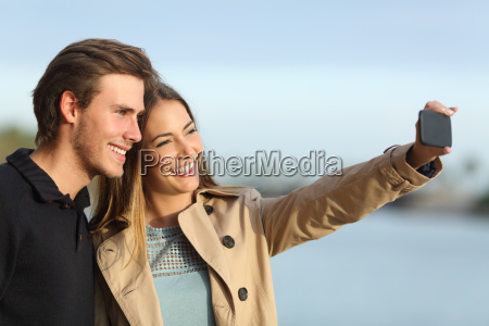 happy couple photographing a selfie with