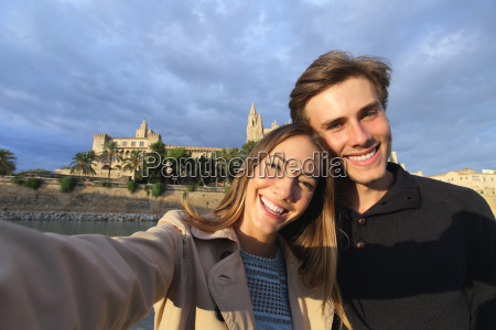 tourist couple on holidays photographing a
