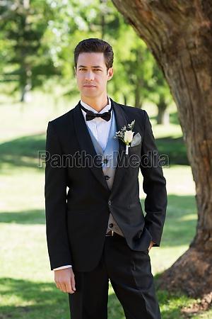 vertrauter braeutigam in tuxedo am garten
