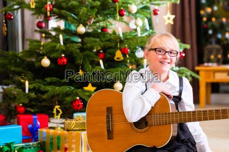 maedchen spielt gitarre an heiligabend