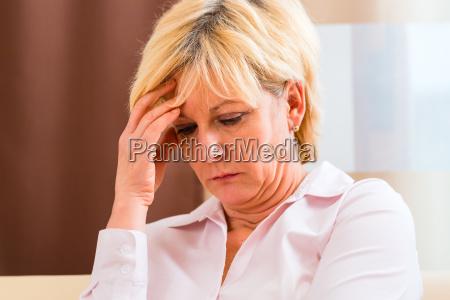 seniorin fasst sich mit kopfschmerzen an