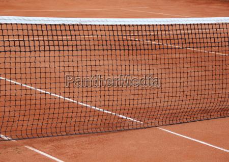tennisnetz auf leerem roten kiesplatz