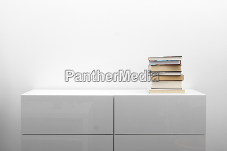 white commode with stack of books