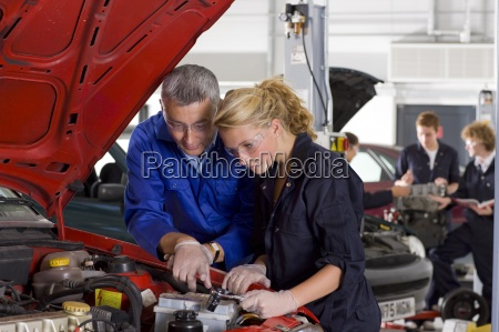 teacher helping student repair car in