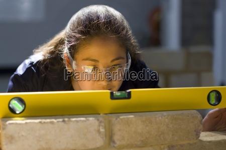bricklaying schueler mit niveau auf backsteinmauer