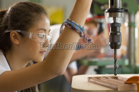 serious student using drill in vocational
