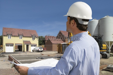 construction worker holding blueprints standing on