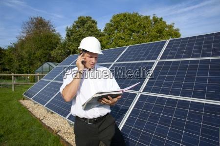 technician holding blueprints standing near large