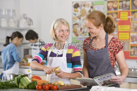 smiling teacher helping student with recipe