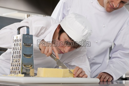 chef watching trainee slice cheese in