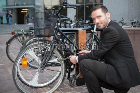geschaeftsmann entsperren seinem fahrrad nach einem