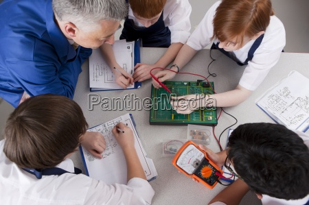 teacher watching students working on electronic