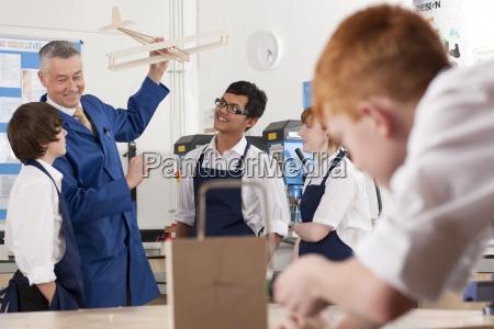 teacher explaining wooden model airplane to