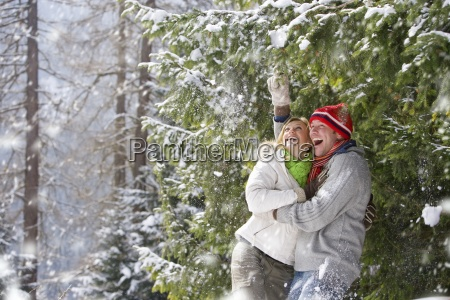 snow falling on happy couple standing