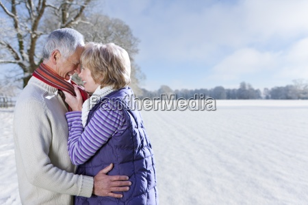 smiling senior couple hugging in sunny