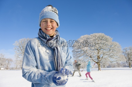 portrait of smiling boy holding snowball
