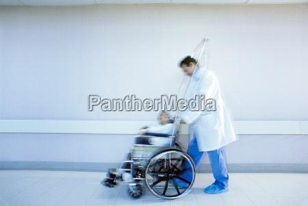 doctor pushing boy in wheelchair in