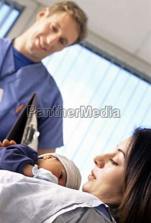 doctor looking down at mother holding