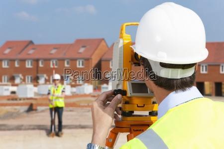 surveyor looking towards co worker through